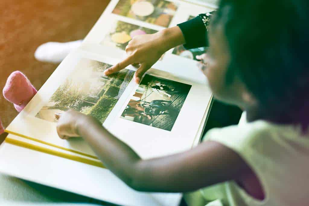 Little girl looking at a photo album with her sibling