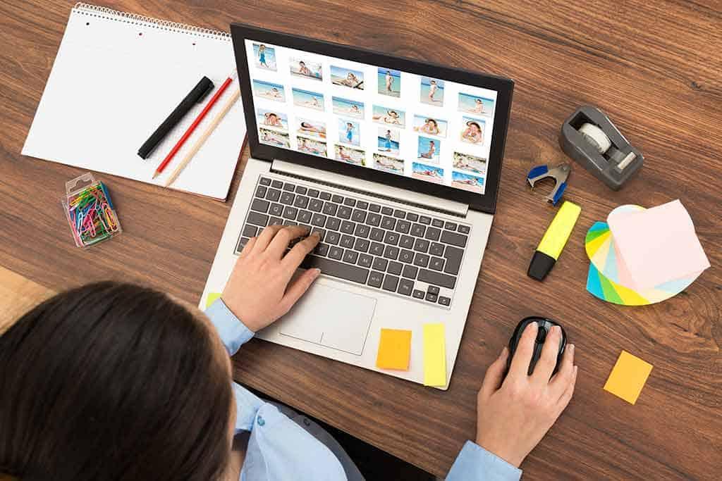 Woman at her laptop browsing through digital photos