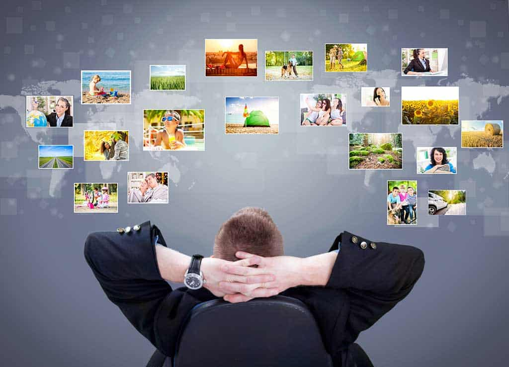 Man sitting back in a chair with arms behind his head looking up into the sky at all his organized photos