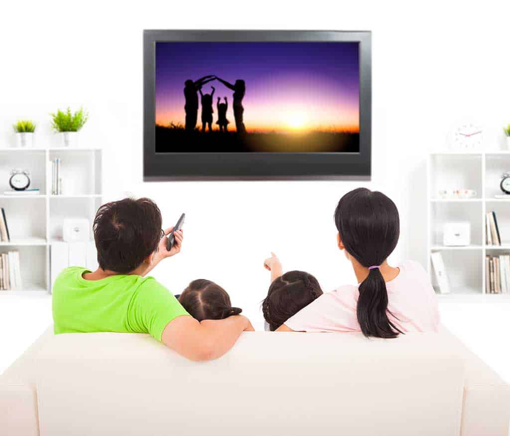 Image of a family watching their travel photos on a television screen on the wall